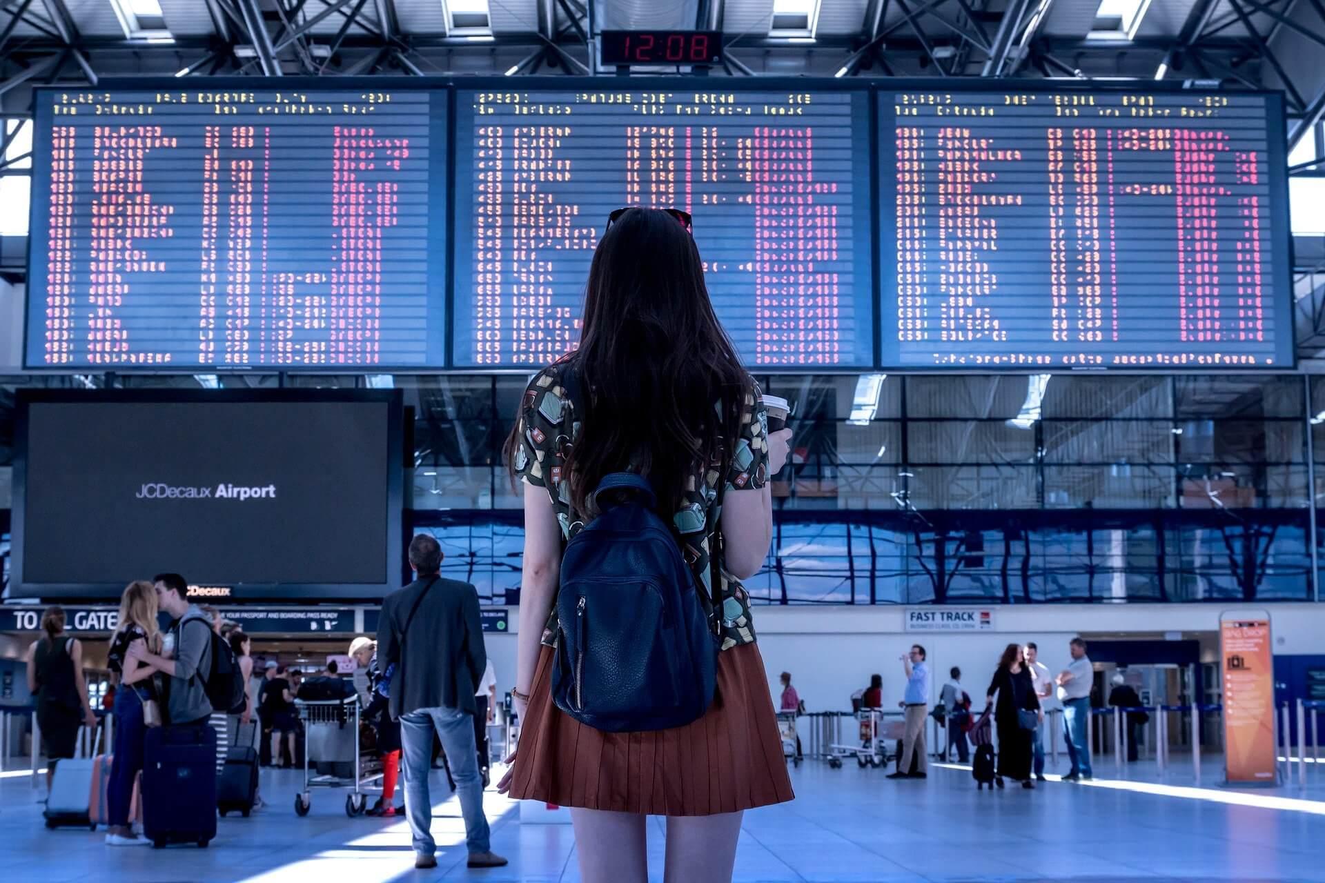 Une femme situé devant le panneau d'affichage d'un aéroport