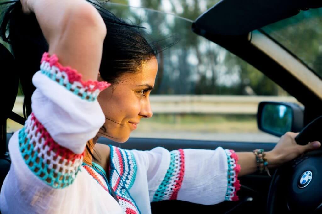 Femme heureuse conduisant une voiture bmw