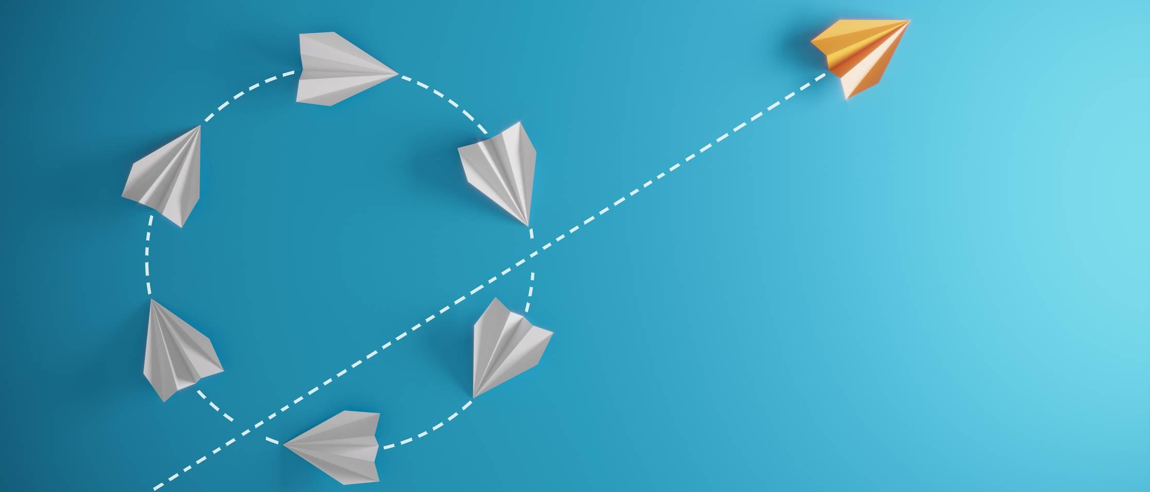 Des avions en papier blanc et un avion en orange