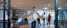 Des salariés en entreprise masqués portant des cartons de déménagement