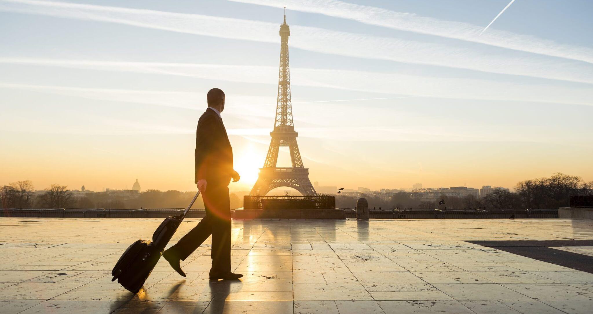 Homme avec valise devant la tour Eiffel
