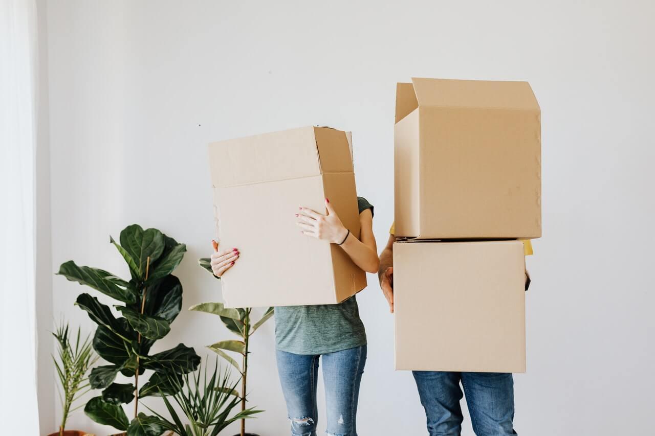 Un couple portant des cartons de déménagement